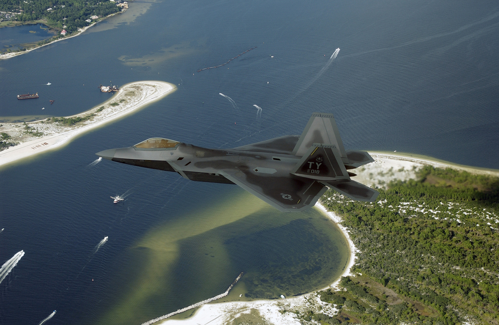 """US Air Force (USAF) Lieutenant Colonel (LTC) Jeffrey """"Cobra"""" Harrigian, Commander, 43rd Fighter Squadron (FS), 325th Fighter Wing (FW), Air Education and Training Command (AETC), Tyndall Air Force Base (AFB), Florida (FL), flies Raptor 01-018, over the Florida (FL) coast line. This is the first of 48 new USAF F/A-22 Raptors assigned to Tyndall's 325th FW. The flight, took place September 26, 2003, is a major milestone and will now enable the 43rd FS to begin formally training pilots to fly this next-generation fighter. The F/A-22 combines stealth, supercruise, maneuverability and many other features enabling a first look, first shot, first kill capability that will provide continued air..."""