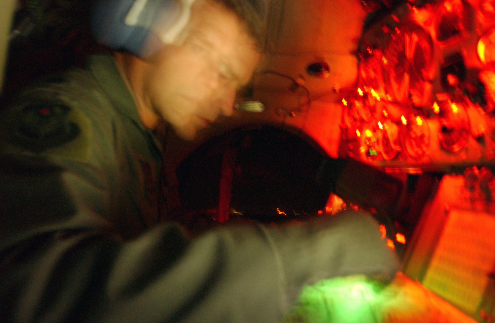 A time exposure blurs a US Air Force (USAF) Navigator as he makes navigational calculations at his station onboard an Antonov AN-32 Cline aircraft during a night flight from Hurlburt Field, Florida (FL) flightline during nighttime operations. The Cline is a Russian built aircraft used by the 6th Special Operations Squadron (SOS)