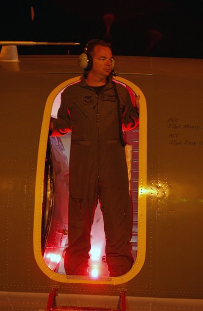 US Air Force (USAF) Technical Sergeant (TSGT) Ty (last name unreleased), Loadmaster, 6th Special Operations Squadron (SOS), leans out of the crew entry door during a safety check prior to engine start on an Antonov AN-32 Cline aircraft during nighttime operations at Hurlburt Field, Florida (FL). The Antonov AN-32 Cline is a Russian built aircraft used by the 6th SOS