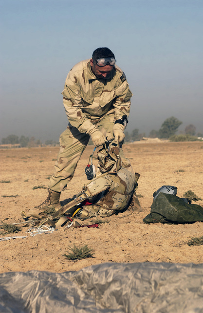 US Air Force (USAF) CHIEF MASTER Sergeant (CMSGT) Tim Malloy assigned to the 101st Expeditionary Rescue Squadron (ERS) as a Pararescueman, packs away his chute at the landing point at Baghdad International Airport (BIA), Iraq (IRQ), as he successfully completes his final jump prior to retirement after 27 years of service, during Operation IRAQI FREEDOM