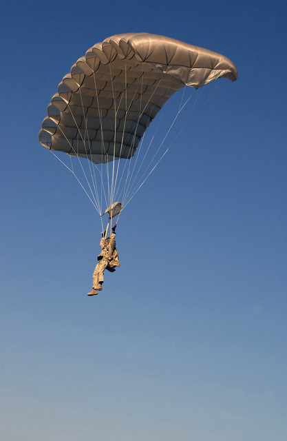 US Air Force (USAF) MASTER Sergeant (MSGT) Jeff Baker, with the 101st Expeditionary Rescue Squadron (ERS) as a Pararescueman, glides into the landing point at Baghdad International Airport (BIA), Iraq (IRQ), as he successfully completes his final jump prior to retirement after 27 years of service, during Operation IRAQI FREEDOM