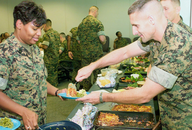US Marine Corps (USMC) Colonel (COL) Michael L. Hawkins (left), Commander, Marine Manpower Officer Assignments, serves food to MASTER Sergeant (MSGT) Rochelle M. Edwards (left), during her Retirement Celebration held at the Marine Manpower Officer Assignments division, aboard Marine Corps Base Quantico, Virginia (VA)
