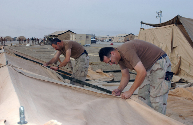 US Air Force (USAF) Technical Sergeant (TSGT) Joseph Dellavalle, right and TSGT Mark D'Elia from the 914th Air Reserve Wing (ARW), Niagara Falls Joint Air Station (JARS), New York (NY), laces up a Temper Tent during construction of 30 new tents for a C-130 Hercules aircraft squadron area being established at Tallil Air Base (AB), Iraq (IRQ), in support of Operation IRAQI FREEDOM