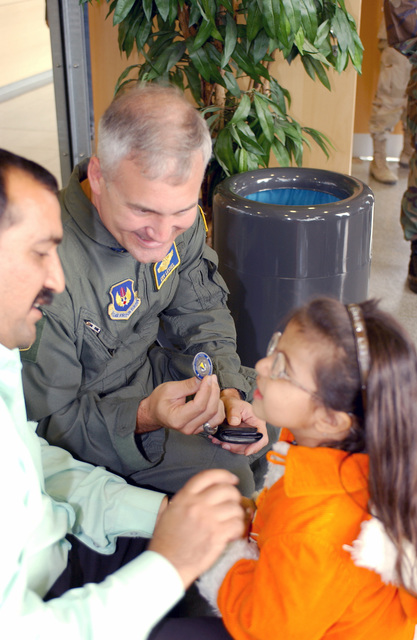 US Air Force (USAF) Brigadier General (BGEN) Erwin F. Lessel III, the 86th Airlift Wing (AW) Commander, at Ramstein Air Base (AB), Germany (DEU), gives a coin to Maraim, 4, one of the 18 Iraqi children flown in from Baghdad International Airport (BIA), for medical care from hospitals throughout Rheinland-Pfalz, DEU