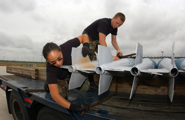 US Air Force (USAF) AIRMAN First Class (A1C) Kristin Delgado and AIRMAN (AMN) Zack Pickeral, assigned to the 7th Munitions Squadron (MS), tie-down munitions on a trailer before transporting them to the flightline for delivery during a Surge Exercise at Dyess Air Force Base (AFB), Texas (TX)