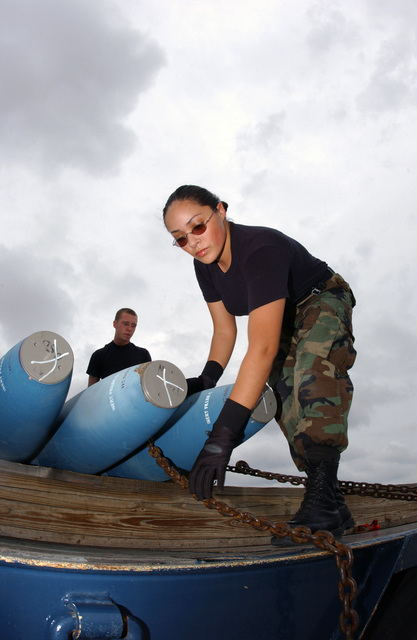 US Air Force (USAF) AIRMAN First Class (A1C) Kristin Delgado, right, and AIRMAN (AMN) Zack Pickeral, assigned to the 7th Munitions Squadron (MS), tie-down munitions on a trailer before transporting them to the flightline for delivery during a Surge Exercise at Dyess Air Force Base (AFB), Texas (TX)