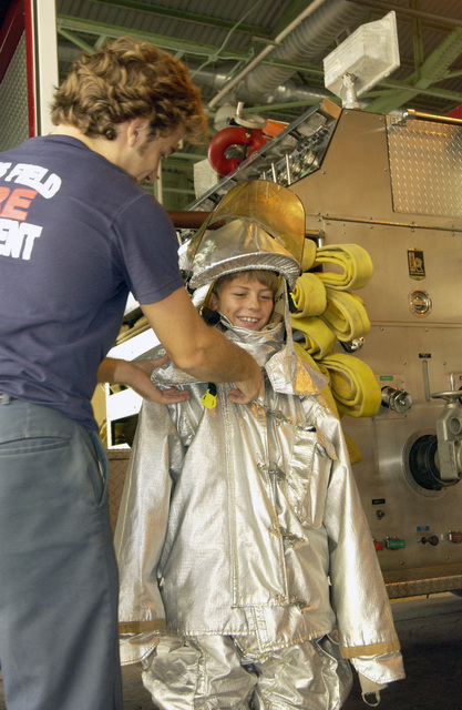 Mr. Bruno Medeiros, a US Air Force (USAF) civilian with the 65th Civil Engineering Squadron (CES), a Fire Fighter at Lajes Field, Azores, Portugal (PRT), helps Julio Aguiar a visiting student from the Juncal elementary school put on a fireproof suit