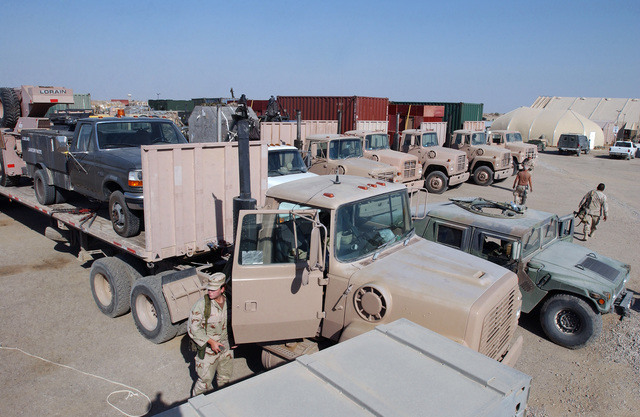 The trucks of the Red Tail convoys gather at a cargo delivery area, on Tallil Air Base (AB), Iraq (IRQ) to deliver provisions to Kirkuk Air Base (AB) and Baghdad International Airport (BIA) in support of Operation IRAQI FREEDOM