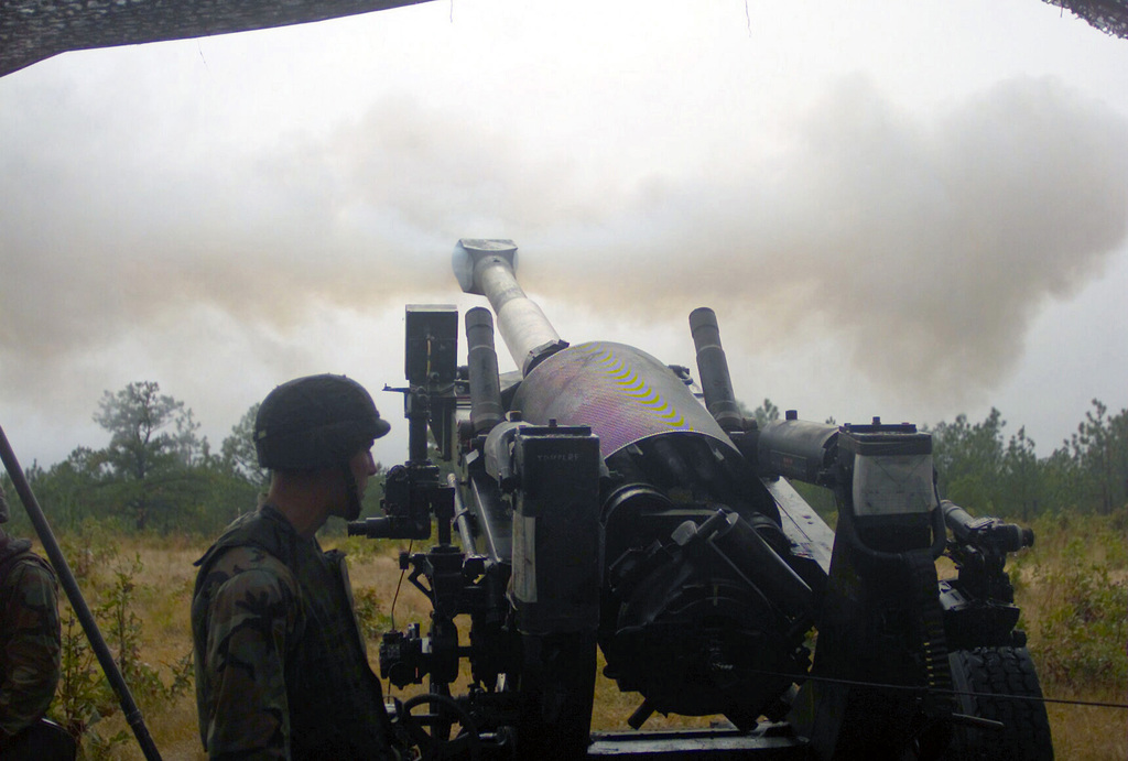 At Fort Bragg, North Carolina, US Marine Corps (USMC) personnel with the 10th Marines, 2nd Marine Division, fire a 96 pound 155mm artillery round from an M198 Towed Howitzer, during Exercise ROLLING THUNDER 2003. (Substandard image)