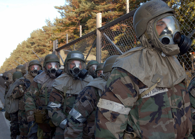 US Air Force (USAF) personnel deployed in support of Exercise Silver Flag wait to process through a Chemical Containment Area and decontaminate their Mission-Oriented Protective Postures level-4 (MOPP-4) gear