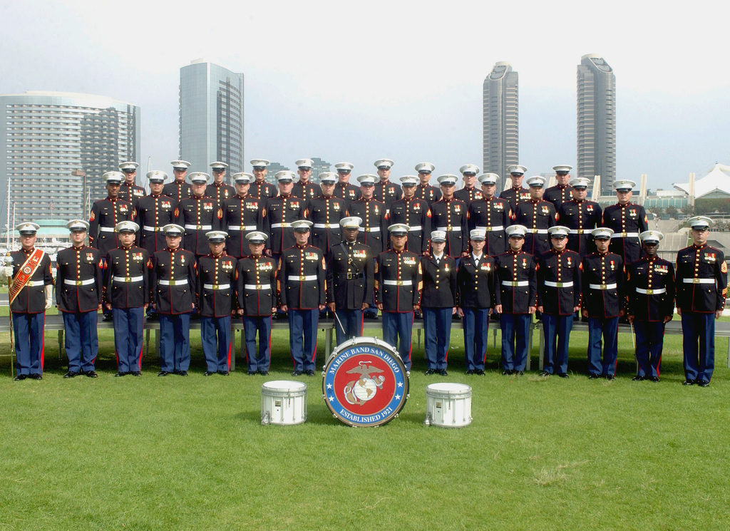 The US Marine Corps (USMC) Band from Marine Corps Recruit Depot (MCRD) San Diego, California (CA) poses for a group photo, with the San Diego City skyline in the background
