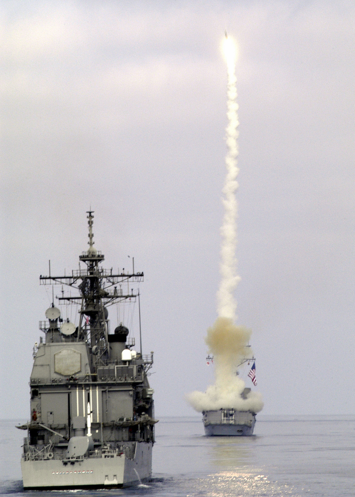 The US Navy Arleigh Burke Class Guided-Missile Destroyer USS PREBLE (DDG 88) fires a surface-to-air Standard Missile-2 (SM-2) missile while conducting missile-firing exercises off the coast of Southern California. The USN Ticonderoga Class Guided Missile Cruiser, also participating in the exercise, observes the launch
