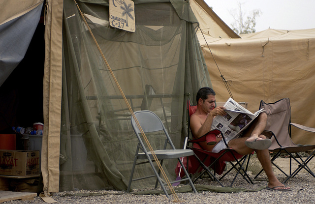 US Air Force (USAF) MASTER Sergeant (MSGT) Joseph Vanpimxteren of the 437th Aircraft Maintenance Squadron (AMXS), Charleston Air Force Base (AFB), South Carolina (SC), reads the Stars and Stripes newspaper by his billeting tent at Camp Sather, Iraq (IRQ)