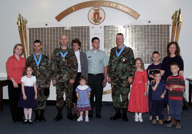 US Army (USA) Soldiers pose for a photograph with their family members during an Induction Ceremony into the Sergeant Audie Murphy Club at Fort Gordon, Georgia (GA). Soldiers Pictured left-to-right: USA STAFF Sergeant (SSG) Gregory Celesky, B Company, 67th Signal Brigade; SSG Larry Bull, E Company, 447th Signal Brigade; and Sergeant (SGT) John Schreier, 447th Signal Brigade. (SUBSTANDARD)