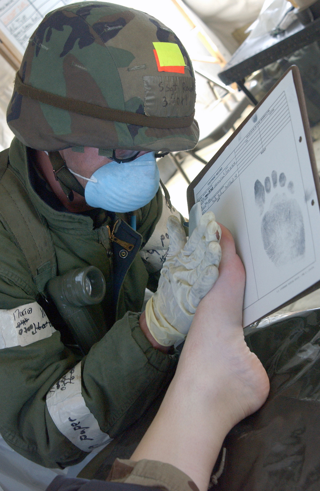 Wearing a protective dust mask, US Air Force (USAF) STAFF Sergeant (SSGT) David Rawls from the 366th Services Squadron (SS) gets footprints from a fallen comrade during Exercise Coronet White, the wing's Operational Readiness Inspection (ORI) exercise