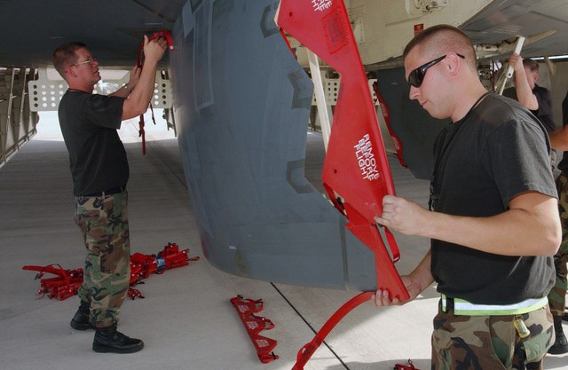 """US Air Force (USAF) Technical Sergeant (TSGT) Steve McElwain, left and SENIOR AIRMAN (SRA) Jason Capehart place the landing door edge covers on the landing gear doors of their B-2 Spirit bomber, """"The Spirit of Pennsylvania,"""" at Nellis Air Force Base (AFB), Nevada (NV). B-2 bombers often particapate in Red Flag exercises on the Nellis air ranges"""