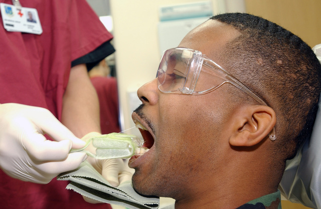 US Air Force (USAF) SENIOR AIRMAN (SRA) Victor Carmona, a Dental Technician with the 48th Dental Squadron (DS), extracts a fluoride mouth tray during a routine dental exam and cleaning on SRA Lance Mitchell, with the 95th Reconnaissance Squadron (RS), at the Royal Air Force (RAF) Mildenhall, England (ENG)