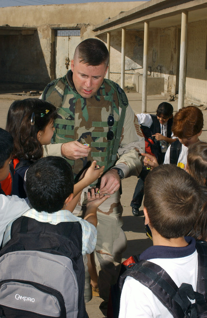 US Air Force (USAF) MASTER Sergeant (MSGT) Robert Frank, First Sergeant for the 380th Expeditionary Mission Support Group (EMSG), hands out candy to Iraqi school children at a school in Kirkuk, Iraq (IRQ), during Operation IRAQI FREEDOM