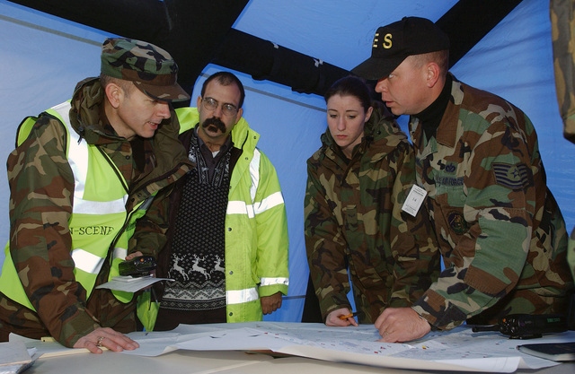 US Air Force (USAF) Colonel (COL) Michael Pasquin, left, the 100th Mission Support Group (MSG) Commander at Royal Air Force (RAF) Mildenhall, England (ENG), is briefed by Technical Sergeant (TSGT) Ron Ennis, of the 100th Civil Engineering Squadron (CES), during a simulated fuel spill exercise