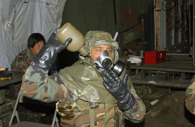 US Air Force (USAF) Technical Sergeant (TSGT) Jerry Arp, a Communications-Computer Systems Operations Craftsman, with the 606th Air Control Squadron (ACS), Spangdahlem Air Base (AB), Germany (DEU), drinks water from his canteen while wearing his Mission-Oriented Protective Postures (MOPP) gear, during a simulated chemical weapons attack in support of Exercise Autumn Warrior '03