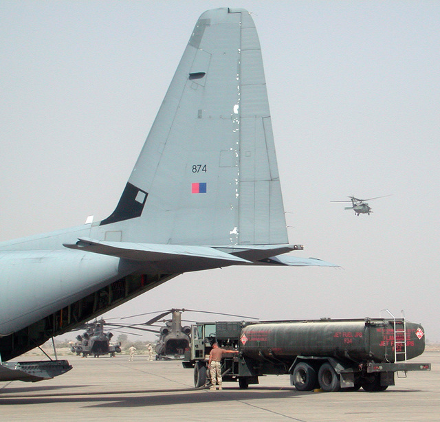 A coalition New Zealand Air Force (NZAF) C-130 Hercules cargo aircraft is fueled by a US Air Force (USAF) Petroleum, Oils and Lubricants (POL) troop, at Baghdad International Airport (BIA), in support of Operation IRAQI FREEDOM