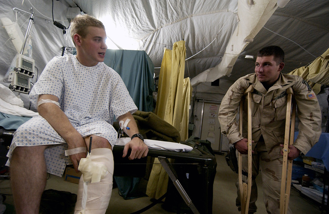US Army (USA) Private First Class (PFC) Casey Nally, left, with the 2nd Battalion, 15th Field Artillery Regiment, Fort Drum, New York (NY), jokes with a friend before being medically evacuated by the 506th Air Expeditionary Medical Squadron (AEMS), at Kirkuk Air Base (AB), Iraq (IRQ), during Operation IRAQI FREEDOM