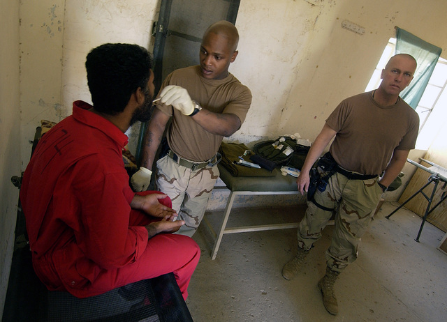 US Army (USA) Sergeant (SGT) Elmore Curtis (center) and USA Captain (CPT) Barry Seip (right) with Task Force 1ST Battalion, 63rd Armor (1-63), provide medical treatment to a detainee at Camp Renegade, the USA 173rd Airborne Brigade's (AB) Collection Facility inside Kirkuk Air Base (AB), during Operation IRAQI FREEDOM