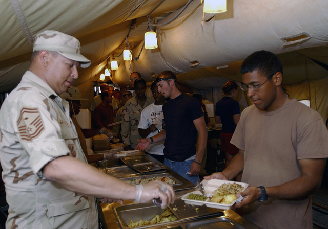 US Air Force (USAF) SENIOR AIRMAN (SRA) Steven Porter receives a helping of dinner from USAF SENIOR MASTER Sergeant (SMSGT) Marc Galbreth, First Sergeant, 447th Civil Engineer Squadron (CES), at the Baghdad Bistro Dining Facility during Operation IRAQI FREEDOM. SMSGT Galbreth volunteered his time to the 447th Expeditionary Services Squadron (ESVS) to serve dinner to the troops