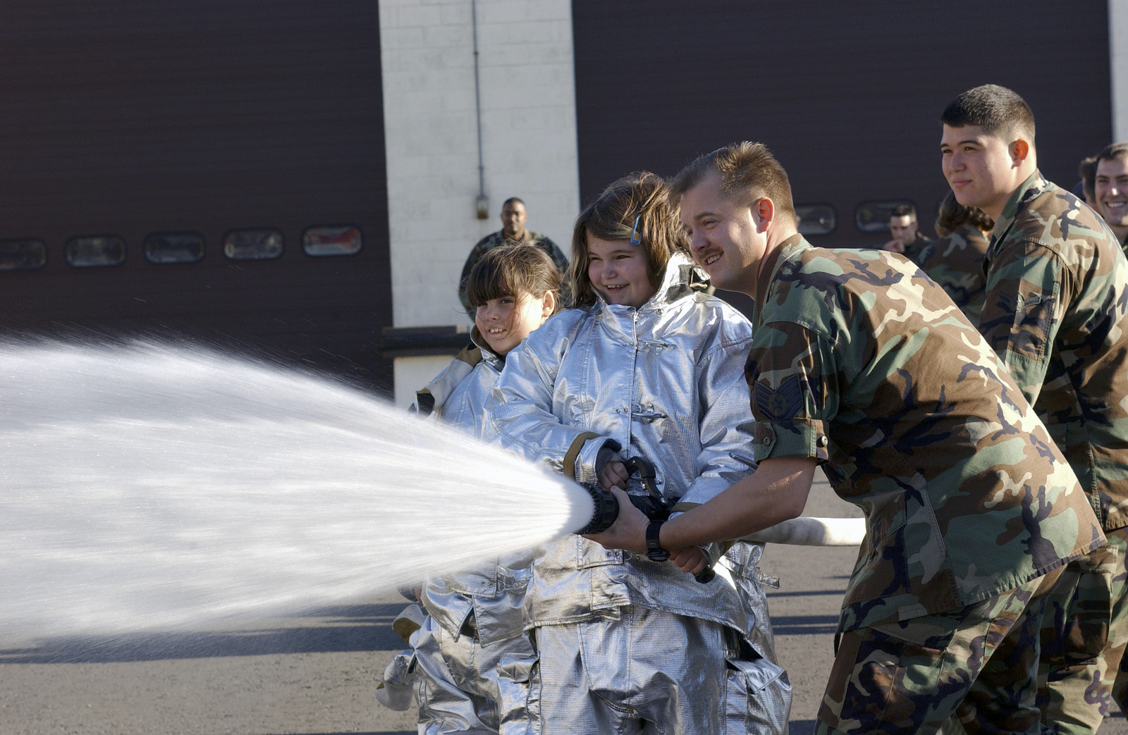 US Air Force (USAF) Technical Sergeant (TSGT) Coben D. Scott, 100th Civil Engineer Squadron (CES), Royal Air Force (RAF) Mildenhall, United Kingdom (UK), gives 10-year-old Olivia Grosvenor training on the fire hose as part of certifying her to be a firefighter during the Pilot for a Day program. Both Olivia and her sister Molly are dressed in JFIRE (Joint Firefighters Integrated Response Ensemble) suits. The program provides children diagnosed with serious or chronic illnesses to fulfill their aviation dreams