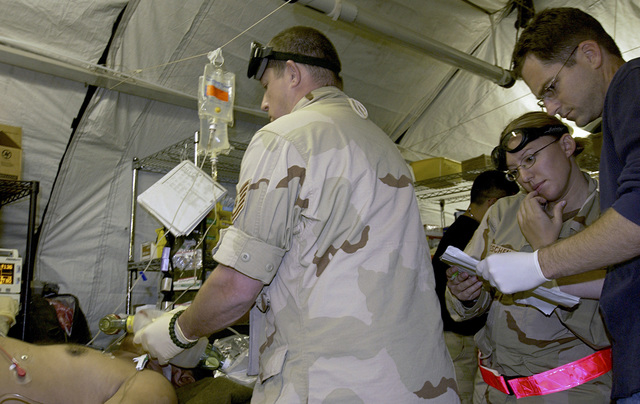 US Air Force (USAF) Major (MAJ) Rob Noll (right), General Surgeon, 447th Expeditionary Medical Squadron (EMDS), reviews a medical chart while treating a non-coalition casualty for a gunshot wound at Baghdad International Airport (IAP), Iraq during Operation IRAQI FREEDOM