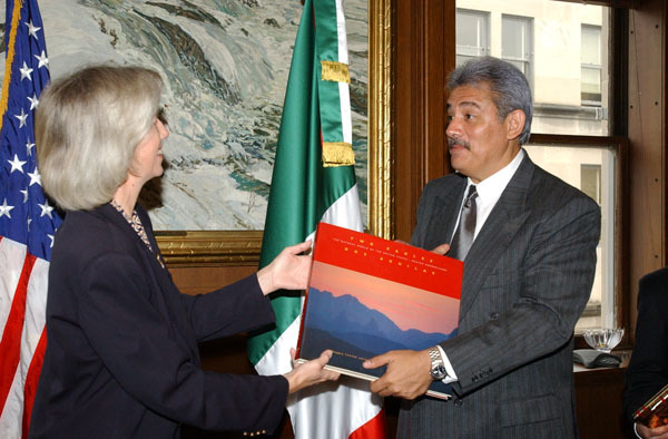 Secretary Gale Norton, left, presenting book, Two Eagles-Dos Aguilas: A Natural History of the U.S.-Mexico Borderlands, to Mexico's Secretary of Environment and Natural Resources, Alberto Cardenas-Jimenez, at Department of Interior headquarters signing event for U.S.-Mexico wildlife protection pact