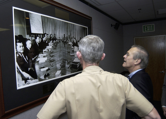 The Honorable Donald H. Rumsfeld (right), U.S. Secretary of Defense, and U.S. Navy Rear Adm. Patrick Dunne (left), Commander, U.S. Naval Forces, Marianas, examine a photograph of the Vietnam Summit, that was held on Guam and hosted by President Lyndon Baines Johnson in 1967, during a brief stopover at Santa Rita, Guam, on Nov. 14, 2003. Secretary Rumsfeld is on his way to official meetings in both Japan and the Republic of Korea. (DoD photo by PETTY Officer 2nd Class Nathanael T. Miller) (Released)