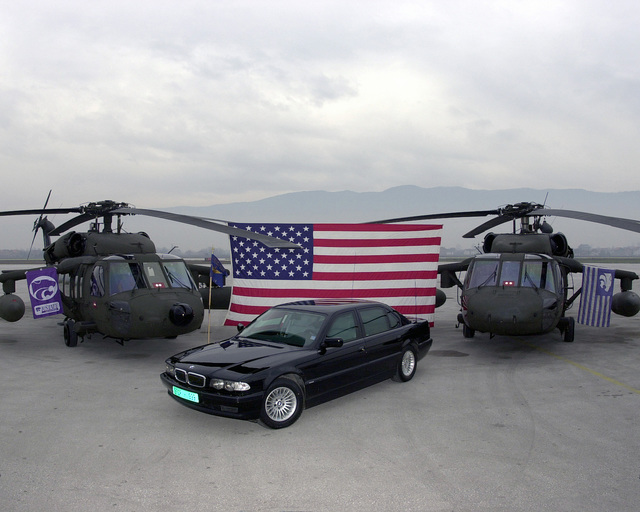 Two US Army UH-60L Black Hawk helicopters, draped with Kansas State University flags, embrace the American Flag for a photo of the General's armored BMW. Image taken during Operation JOINT FORGE