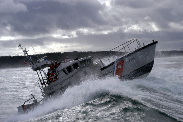 US Coast Guard (USCG) 47-foot Motor Lifeboat (MLB) (47268) breaks a wave during a rescue at sea exercise off the coast of Yaquina Bay State Park, Oregon (OR). Coast Guard personnel train regularly in all types of weather and sea conditions