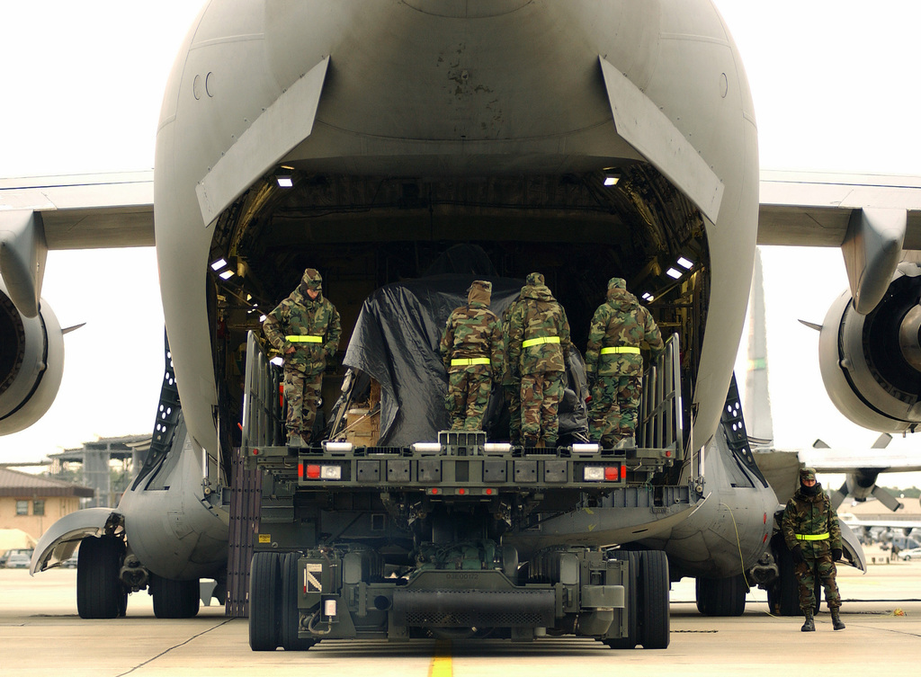 US Army (USA) Soldiers, 82nd Airborne Division (AB DIV), Fort Bragg, North Carolina (NC), onboard a Tunner 60K Loader prepare to load a 155mm Howitzer onto a US Air Force (USAF) C-17A Globemaster III at Pope Air Force Base (AFB), North Carolina (NC). The weapon will be air dropped as part of a multi-ship formation during Large Package week. Large Package week is a joint exercise between the USAF and the USA, designed to enhance interservice cohesiveness