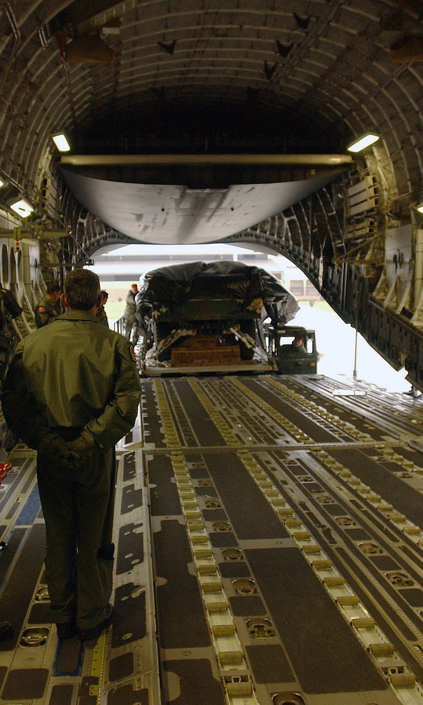 A US Air Force (USAF) Loadmaster, 16th Airlift Squadron (AS), Charleston Air Force Base (AFB), South Carolina (SC), watches as US Army (USA) Soldiers, 82nd Airborne Division (AB DIV), Fort Bragg, North Carolina (NC), help load a wrapped 155mm Howitzer onto a USAF C-17A Globemaster III at Pope AFB, NC. The weapon will be air dropped as part of a multi-ship formation during Large Package week. Large Package week is a joint exercise between the USAF and the USA, designed to enhance interservice cohesiveness