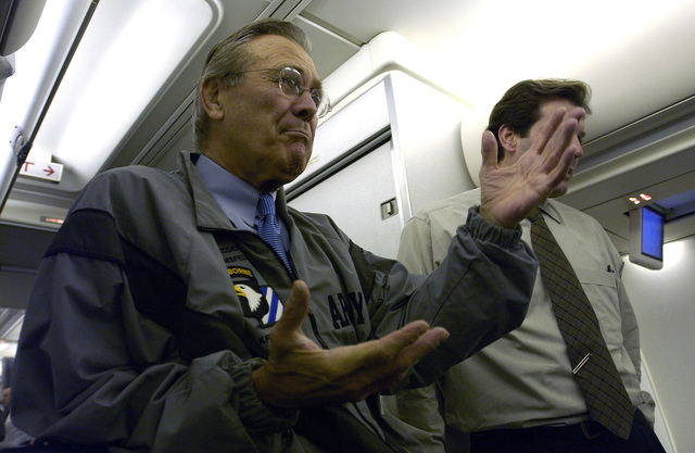 The Honorable Donald H. Rumsfeld (left), U.S. Secretary of Defense, and Lawrence Di Rita (right), Acting Assistant Secretary of Defense for Public Affairs, meet with the traveling press during a flight on a C-32 aircraft to Baku, Azerbaijani, on Dec. 3, 2003. (DoD photo by TECH. SGT. Andy Dunaway) (Released)