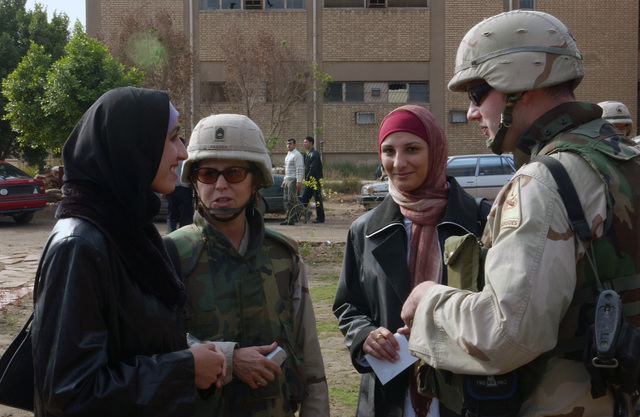 US Army (USA) Sergeant First Class (SFC) Vanessa Peeden (left), 372d Mobile Public Affairs Department (MPAD), and USA Lieutenant LT Alex Kasarda, Headquarters and Headquarters Company (HHC), 1ST Brigade (BDE), Brigade Public Affairs Officer (PAO), speak with Iraqi students at a ceremony celebrating the re-opening of the Baghdad University Museum of Natural History and Internet Cafe in Baghdad, Iraq. The museum and internet cafe were rebuilt using $40,000 of the Commanders' Emergency Relief Program (CERP) funds from the US Army's 1ST Armored Division (AD) during Operation IRAQI FREEDOM