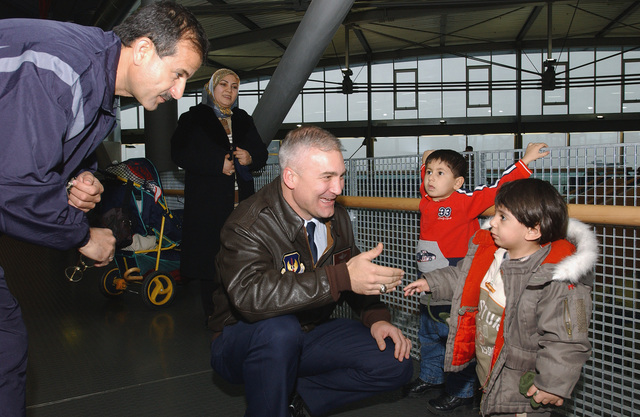 US Air Force (USAF) Brigadier General (BGEN) Erwin F. Lessel III, Commander, 86th Airlift Wing (AW), greets two-year-old Zain Al Abedin Asadi at the Ramstein Air Base (AB) Passenger Terminal waiting area as his mother looks on. Asadi completed medical treatment at Landstuhl Regional Medical Center and is on his way home to Nasaria, Iraq