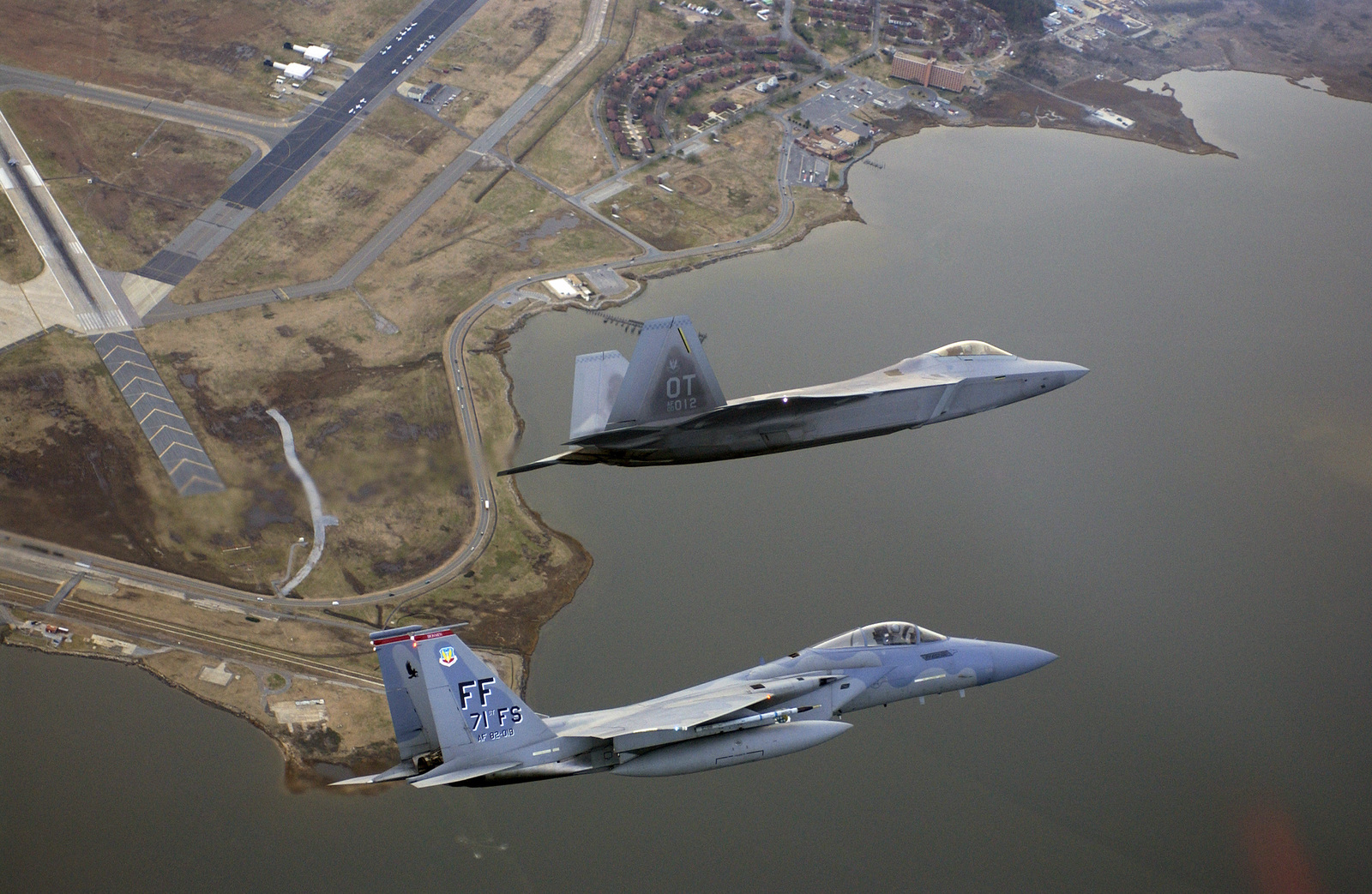 Aerial as US Air Force (USAF) Lieutenant Colonel (LTC) Dave Rose, 422nd Test and Evaluation Squadron (TES), Nellis Air Force Base (AFB), Nevada (NV), pilots the Air Force's new F/A-22 Raptor in formation with an F-15C Eagle piloted by USAF Major (MAJ) Robert Garland, 71st Fighter Squadron (FS), Langley Air Force Base (AFB), Virginia (VA). The two paired up after a historic fly-by by the F/A-22 at the First Flight Centennial Celebration at the Wright Brothers National Memorial in Kill Devil Hills, North Carolina (NC) for a fly-by over the future home of the F/A-22: Langley AFB, VA