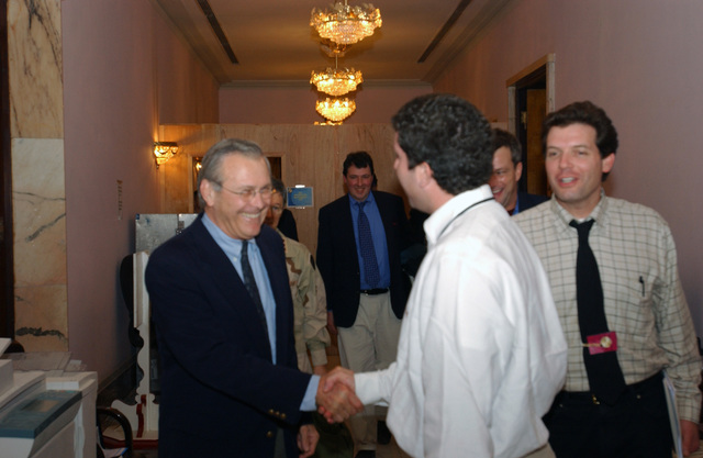 The Honorable Donald H. Rumsfeld (left), U.S. Secretary of Defense, shakes hands with Mr. Christopher M. Harvin (second from right), Director of Advance for Strategic Communication, Strategic Command, inside the Coalition Provisional Authority building, Baghdad, Baghdad Province, Iraq, on Dec. 6, 2003. Secretary Rumsfeld is on his way to hold a press conference during an official visit to Baghdad during Operation Iraqi Freedom. (U.S. Army photo by SPC. Rachel Ahner) (Released)