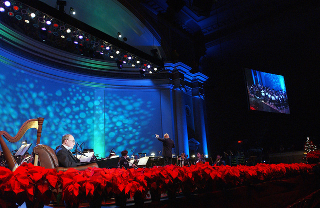 "With Poinsettias lining the stage, US Air Force (USAF) CHIEF MASTER Sergeant (CMSGT) James Queen (seated) performs a reading of ""Yes, Virginia, there is a Santa Claus,"" during the US Air Force Band Christmas concert at Constitution Hall in Washington, DC"