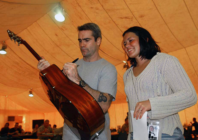 Henry Rollins, Actor and Musician, signs a guitar at a base dining facility for avid fan US Air Force (USAF) AIRMAN First Class (A1C) Catherine Shultz, Civil Engineer Readiness Troop, 379th Expeditionary Civil Engineering Squadron (ECES). Mr. Rollins is one of the many celebrities donating their time and effort to the United Services Organization (USO)/Armed Forces Entertainment tour in support of deployed US military troops