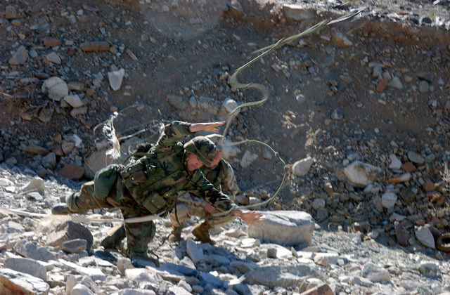 A US Marine Corps (USMC) Instructor look on as a Marine attending the Infantry Officer's Training Course, tosses a grapping hook over a concertina wire barrier, at the platoon based trench and grenade range 410A, located at the Marine Air Ground Combat Center, Twentynine Palms, California (CA)