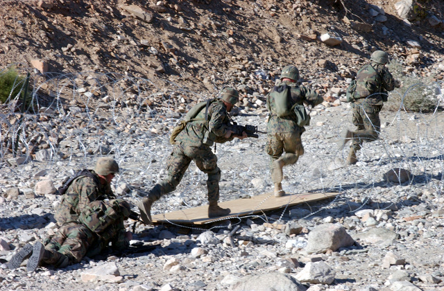 Armed US Marine Corps (USMC) Marines attending the Infantry Officer's Training Course breach a concertina wire barrier, while conducting training at the platoon based trench and grenade range 410A, located at the Marine Air Ground Combat Center, Twentynine Palms, California (CA)