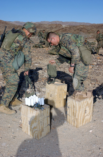 Two US Marine Corps (USMC) Marines attending the Infantry Officer's Training Course, open crates of ammunition as they prepare for the live fire portion of the Infantry Officer's Training Course, being held at the platoon based trench and grenade range 410A, located at the Marine Air Ground Combat Center, Twentynine Palms, California (CA)