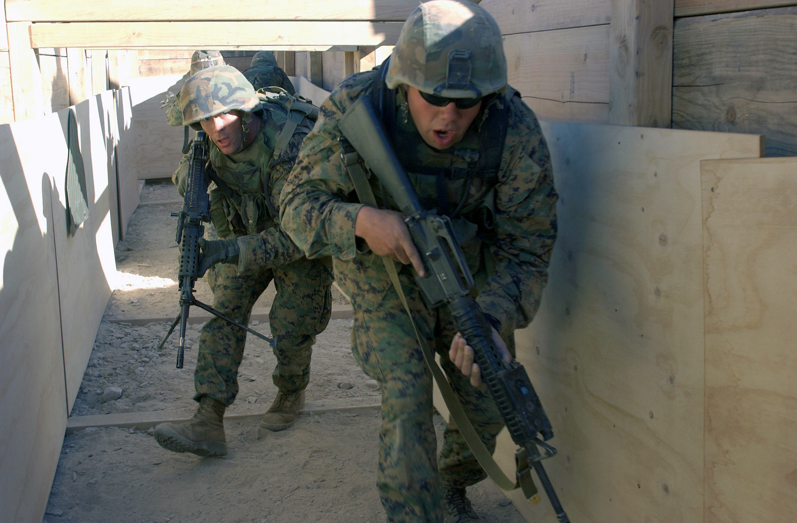 US Marine Corps (USMC) Marines attending the Infantry Officer's Training Course, armed with 5.56mm M16A2 rifles and a M249 Squad Automatic Weapons (SAW), move through a simulated enemy bunker position at the platoon based trench and grenade range 410A, located at the Marine Air Ground Combat Center, Twentynine Palms, California (CA)