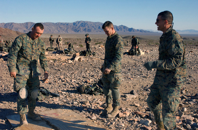 US Marine Corps (USMC) Marines cut a wooden board in half to use for breaching aid, while attending the Infantry Officer's Training Course, at the platoon based trench and grenade range 410A, located at the Marine Air Ground Combat Center, Twentynine Palms, California (CA). Pictured left-to-right are: Second Lieutenant (2LT) Jacobs, 2LT Ryan Gardinier, and 2LT Ilorio Pantano