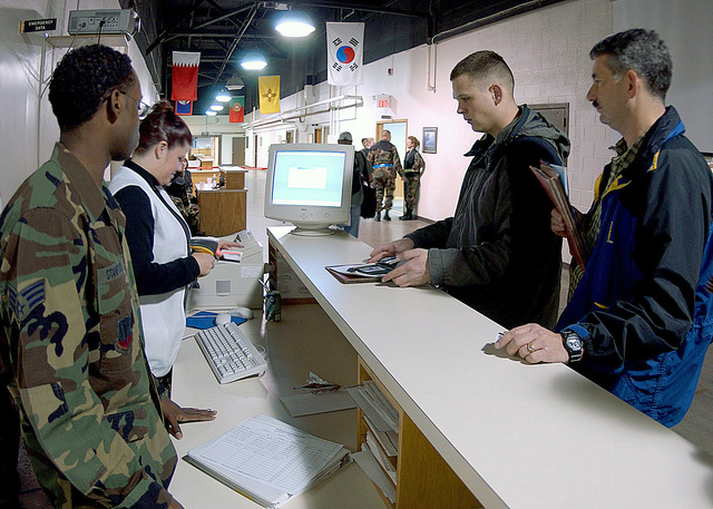 US Air Force (USAF) SENIOR AIRMAN (SRA) David Stanford (far left) 28th Medical Group (MDG) Augmentee, and USAF Technical Sergeant (TSGT) Melody Hester (in white vest) 28th Medical Operations Squadron (MDOS), scan the Military Identification Cards of deploying 28th Bomb Wing (BW) members to verify their immunizations are current. The 28th BW, Ellsworth Air Force Base (AFB), South Dakota (SD), is deploying people and assets to the Central Command (CENTCOM) Area of Responsibility (AOR) in support of Operations ENDURING and IRAQI FREEDOM and the President's Global War on Terrorism (GWOT)