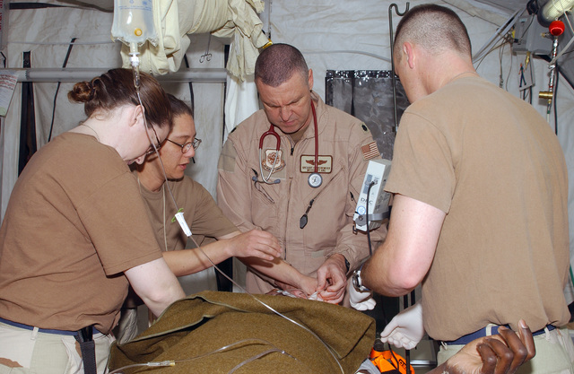 US Air Force (USAF) Technical Sergeant (TSGT) Doria Gregg (left), USAF MASTER Sergeant (MSGT) Debra Alaniz, USAF Lieutenant Colonel (LTC) Gregory Bredemeier, and USAF Captain (CPT) Charles Helms (right), 506th Expeditionary Medical Squadron's (EMDS) Emergency Room (ER) team at Kirkuk Air Base (AB), Iraq. The medical team unbandages a US Army (USA) Soldiers head in preparation for medical attention after arriving at the ER from a motor vehicle accident during Operation IRAQI FREEDOM